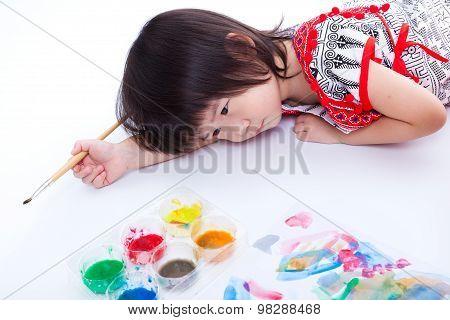 Girl Lying On Floor And Hold Paintbrush. On White. Studio Shot