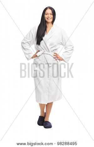 Full length portrait of a cheerful woman in a white bathrobe, looking at the camera and smiling isolated on white background