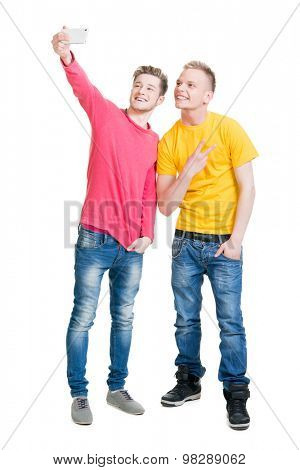 Two happy friends making selfies on isolated background.