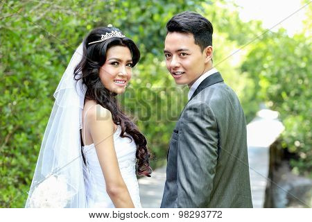 Newlywed Couple Holding Hands And Looking Back