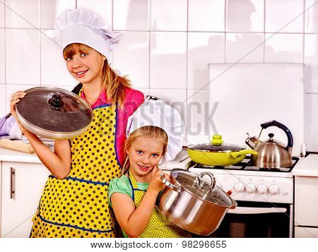 Children wearing hat and apron cooking at kitchen. Kids cooking at home