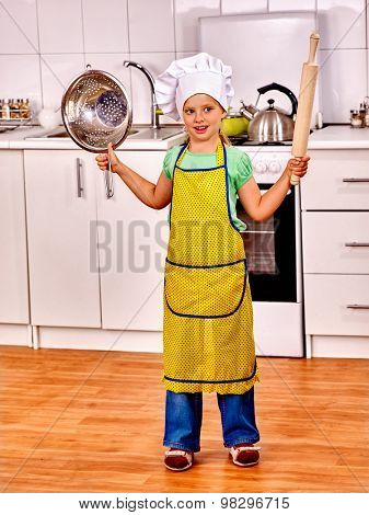 Child wearing hat and apron cooking at kitchen. Children cooking at home