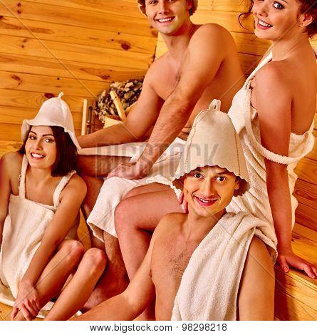 Men and women  in hat  relaxing  together. People in sauna room