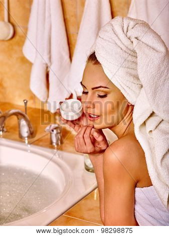Woman applying moisturizer Bathroom cosmetics.