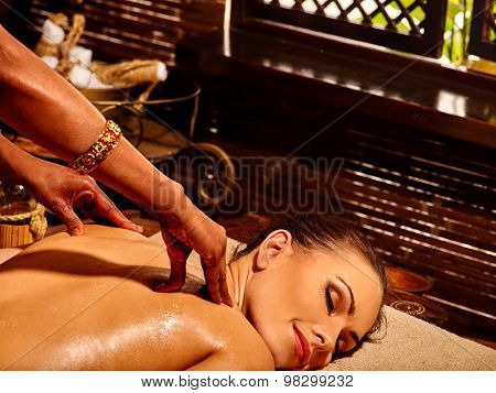 Young woman having oil Ayurveda treatment. Spa resorts in India