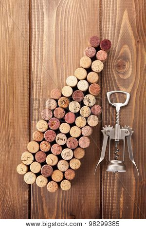 Wine bottle shaped corks and corkscrew over rustic wooden table background. Top view
