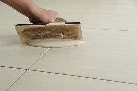 picture of grout  - The hand of man holding a rubber float and filling joints with grout - JPG