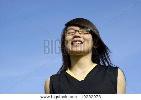 Cheerful asian teen girl and sky