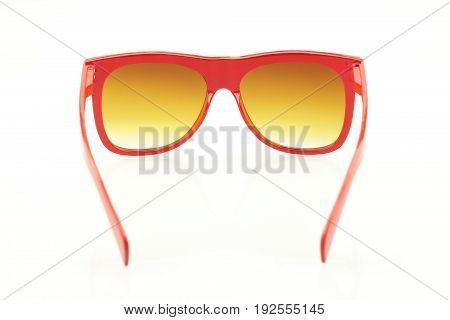 Detail of red eyeglasses on white background