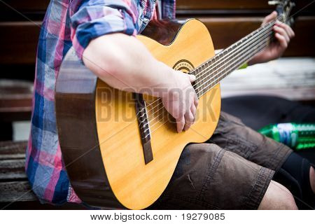 Musician playing guitar on city street