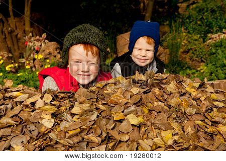 Two happy smiling brothers sit in a heap of colorful autum leaves wearing warm clothes and hats