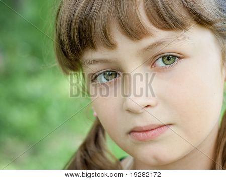 Fullface portrait of serious little girl with beautiful green eyes and blond hair