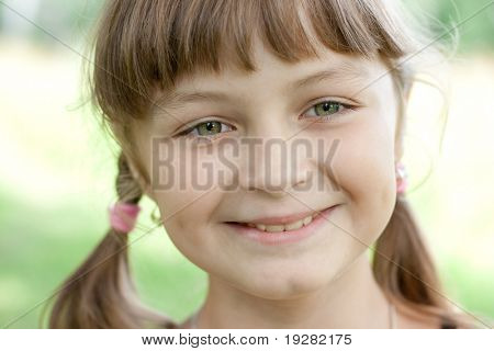 Fullface portrait of smiling little girl with green eyes and blond hair