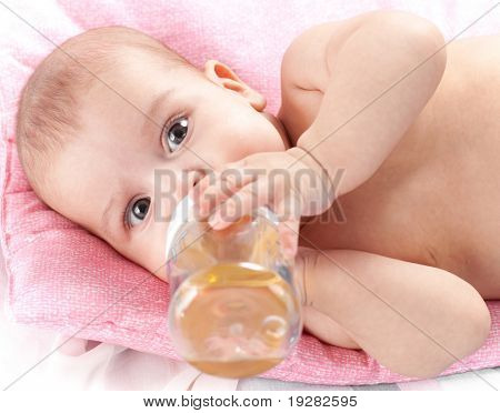 3 months adorable  baby girl drinking from plastic bottle in her bed