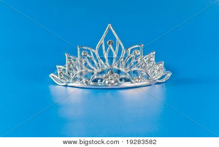 Tiara or diadem with reflection on blue background