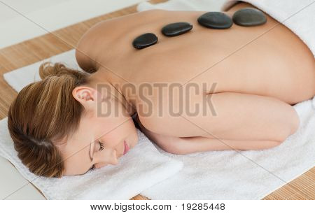 Young woman relaxing while lying with pebbles on her back