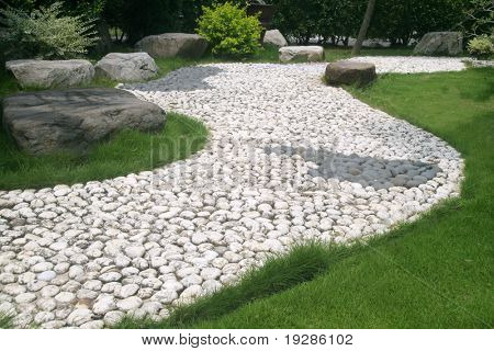 A stone walkway through an Asian garden