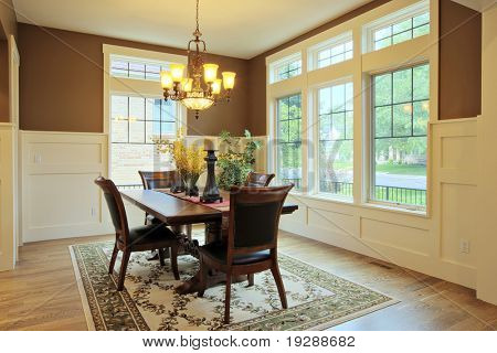 Large dining room with wood floors and area rug