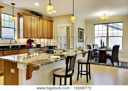 Elegant, brightly lit kitchen with island and light wood cabinetry