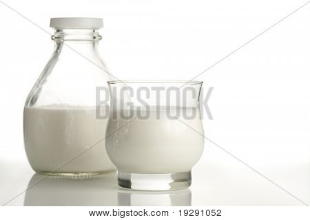 Milk jug and full glass on white background. Focus on front edge of glass.