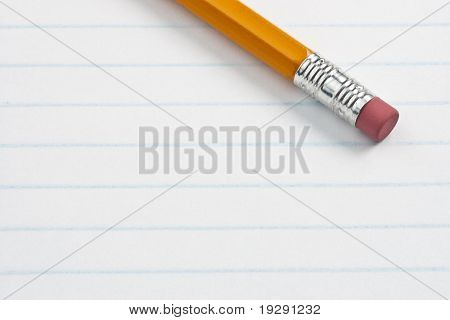 Eraser pencil end on note pad lined paper. Focus on eraser end of pencil.
