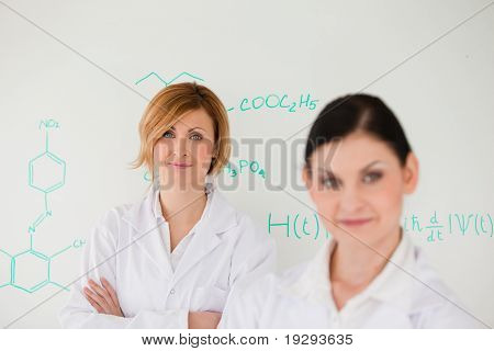 Two women posing in front of a whiteboard
