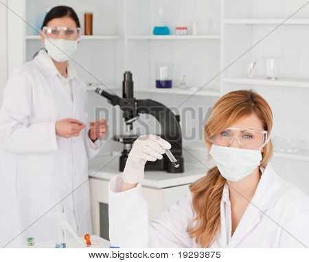 Blonde and dark-haired scientists posing in lab