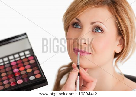 Cute female having her make up done by a make up artist