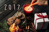 Постер, плакат: 2017 Text Sign New Year Number With Hand Lighting Up Candle And Present Gingerbread Cookies Garnet O