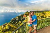 Hawaii travel Napali selfie couple at Napali nature Kauai Hawaii. Young tourists taking selfie phone poster