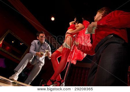 View of two men offering money to a stripper on stage