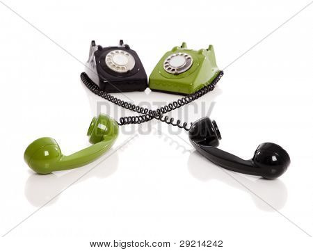 Conceptual image made with two vintage phones isolated on white background