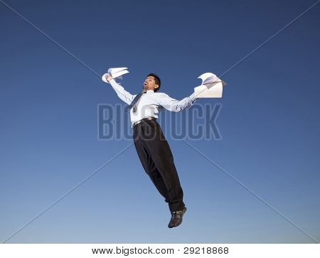 Businessman jumping in the air holding document papers in his hands