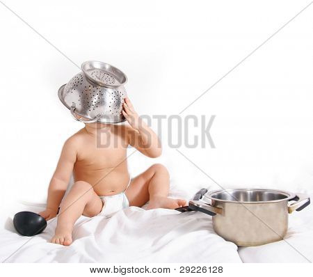 cute infant playing with kitchen utencil