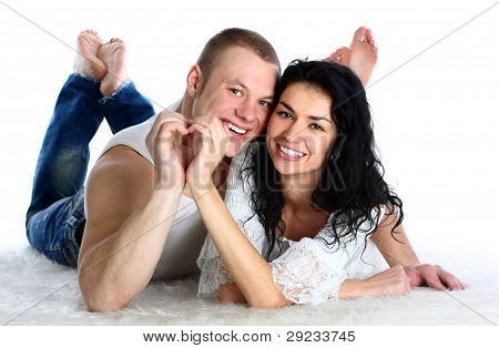 Happy young adult couple lie on the floor nd making heart by hands