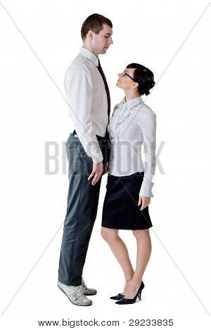 Tall Businessman Standing On Tiptoe Before A Woman