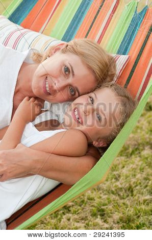 Rest in the garden, happy childhood - girl with mother playing in colorful hammock