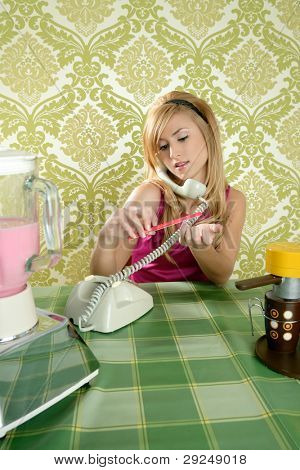 Housewife retro vintage talking phone in kitchen with nail file