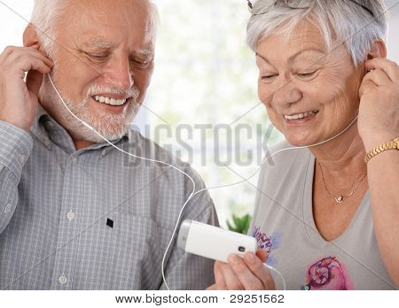 Happy elderly couple using mp3 player, listening to music, smiling.?