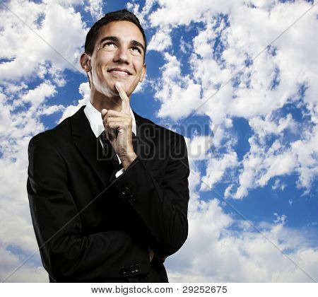 portrait of a young business man thinking against a blue sky background