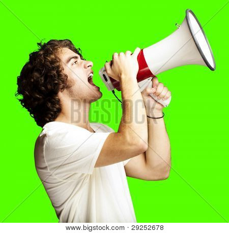 portrait of a handsome young man shouting with a megaphone against a removable chroma key background
