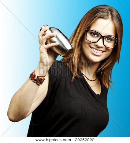 portrait of a young woman shaking a cocktail shaker over a blue background