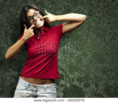 portrait of a happy young woman gesturing with her mouth against a vintage wall