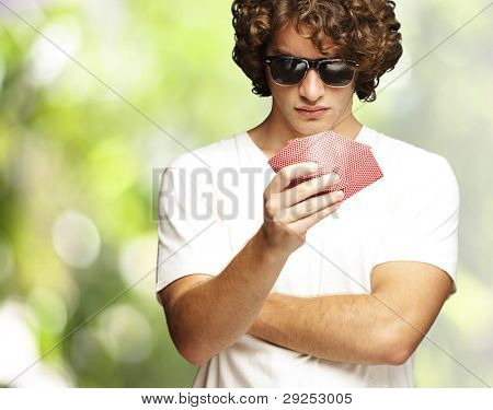 portrait of a young man wearing sunglasses and playing poker against a nature background