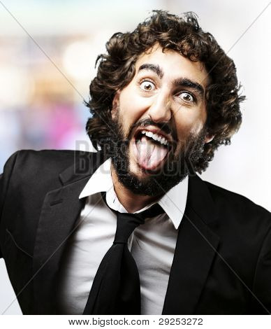 portrait of a young man joking and showing his tongue against an abstract background