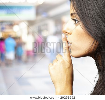 portrait of a young woman doing a silence sign against a crowded place