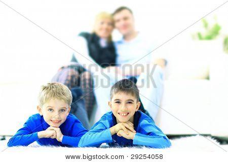Lächeln der Kinder, die auf der Suche nach präsentiert in Christmas Stiefel und Familie auf sofa