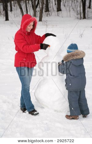 Mother And Child Make Snowman
