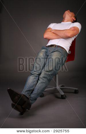 Man Relaxing On Stool On Dark Background In Studio