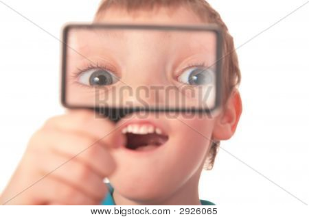 Boy Looks Through Magnifier With Surprise